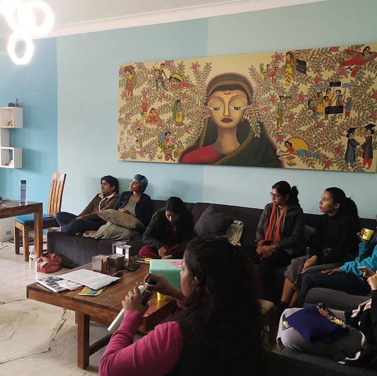 Image of participants sitting in workshop with a wall painting of Savitribai Phule as background